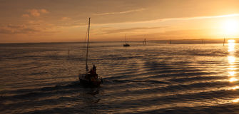 Sailing boat in the sun set Stock Photo