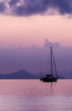 Sailing boat at sunrise. Silhouette of a sailboat in the sea at sunrise Stock Images