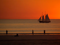 Sailing boat in Sunset, Broome. Ship, people on beach, Australia stock photography