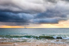 Sailing boat at sunset. Cloudscape over the sea with sailing boat at sunset Royalty Free Stock Photography