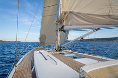 Sailing boat teak deck and hoisted sails, view from the cockpit to the bow. Royalty Free Stock Image