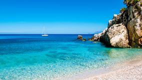 A sailing boat into the turquoise Mediterranean Sea, from a pebbles beach. A sailing boat into the turquoise Mediterranean Sea, view from the beach, with shallow Royalty Free Stock Image