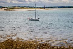 A sailing boat on the water, two obelisks on the beach. royalty free stock image