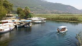Sailing boat. White boat sailing in canal in Akyaka Turkey and many boats standing around. Landscape with mountain and tall grass on background Royalty Free Stock Photos