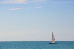 Sailing boat with white sails in the open sea Stock Image