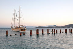 Sailing boat yacht, the ocean and the sunset. Bodrum port, Turkey. Breakwaters with steel posts. Royalty Free Stock Photos