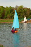 Sailing Boats. Boats sailing on a lake or river with the sails catching the wind whilst another boat gets ready to launch Royalty Free Stock Image