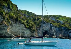 Sailing boats anchored near cliffs. Two vacation sailing boats anchored in clear blue water near cliffs in the Ionian Sea Royalty Free Stock Photos