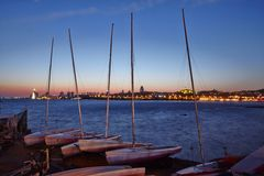 Sailing boats at beach and Qingdao city night scene Royalty Free Stock Photography
