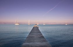 Sailing boats in front of a pier with clear skies in South Corfu Greece.  Royalty Free Stock Photo