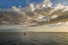 Sailing boats in front of a silhouetted island of Capri Royalty Free Stock Photography