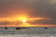 Sailing boats on horizon bathed in sun's rays Royalty Free Stock Images