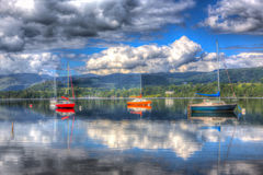 Sailing boats on a lake with mountains on beautiful summer day with cloudscape in HDR Stock Image