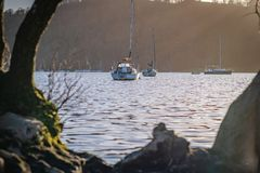 Sailing boats on Lake Windermere, Lake District - early spring Sunset March 2019 stock photos