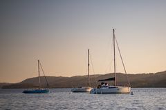Sailing boats on Lake Windermere, Lake District - early spring Sunset March 2019 stock photography