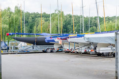 Sailing boats on land. Sailboats ashore on a pitch in the marina on their trailers Stock Images