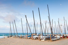 Sailing boats lay in a row on the sandy beach Royalty Free Stock Photos