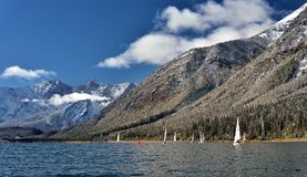 Sailing boats on Lower kananaskis lake in the fall after a fresh snow Stock Photo