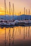 Sailing boats in marina at sunset. Stock Photos