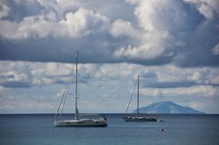 Sailing boats and Montecristo island. On the background, covered by clouds on the top. Italy Royalty Free Stock Photo