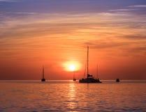 Sailboats at the sunset. Sailing boats at orange sunset. Colorful seascape royalty free stock image