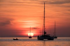 Sailing boats and powerboat at sunset. Colorful seascape stock photos