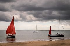 A sailing boats with red sail being moored on a beach. stock images