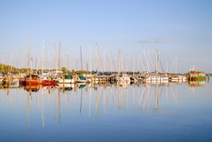 Sailing Boats In A Remotely Located Harbout Reflecting In The Water Surface In The Warm Evening Light. Reflections in this picture are symmetrical and make a royalty free stock images