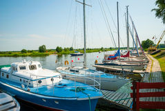 Sailing boats on the river in Silute, Lithuania. View on moored sailboats on river in Silute, Lithuania in sunlight Stock Image