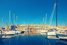 Sailing boats on Senglea marina in Grand Bay, Valetta, Malta. On a bright day. This image is toned Royalty Free Stock Image