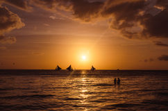 Sailing boats and silhouette of couple over beautiful sunset Stock Image