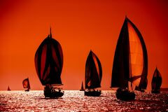 Free Sailing Boats Silhouette In The High Sea On Orange Sunset Stock Photos - 170128353