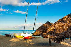 Sailing boats and umbrellas at a beach in Cuba Stock Image