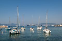 Sailing boats in yacht harbor. Clear blue sky with sailing boats at the Cannes Yacht Club and a cruise ship in the background. Photo taken August 2018 stock images