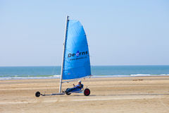 Sailing buggy at beach with blue sky. IJmuiden - The Netherlands - March 20, 2011. Unidentified man sails with buggy at beach competition on March 20,2011 Royalty Free Stock Photo