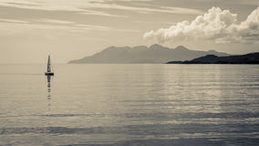 Sailing in Calm Waters. Distant sailboat on calm waters with mountains in the distance in Scotland.  Black and white art Stock Images