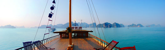 Sailing the calm waters of Halong Bay vietnam on a traditional Junk. Panoramic from the teak deck of a traditional junk as it sails the smooth turquoise waters Royalty Free Stock Image