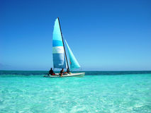 Sailing at the caribbean sea. Blue sailing boat in a beautiful turquoise caribbean sea. Sunny day with a clear sky royalty free stock photography