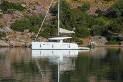Sailing catamaran. View of a sailing catamaran moored in a calm bay, Poros island - Greece Stock Images