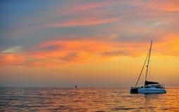 Sailing catamaran at the ocean at the coast of South Africa at sunrise. Sailing catamaran at the ocean at the coast of South Africa at early morning. Before Stock Photography