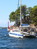 Sailing catamaran sails along the rocky green coast past the red literary sign - the fairway lighthouse. City of Sibenik in the Da stock photo