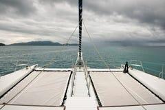 Sailing catamaran towards the rain Stock Images