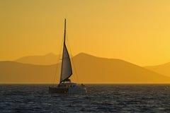 Sailing catamaran. View of a sailing catamaran cruising at sunset, Aegean sea - Greece Royalty Free Stock Images