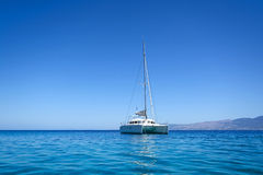 Sailing catamaran. View of a sailing catamaran moored in a calm bay, Pserimos island, Greece Royalty Free Stock Photos