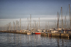 Sailing and engine boats in the harbour channel Royalty Free Stock Images