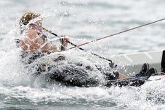 Sailing Finn 03. A Finn sailor crashes through a wave during a race Stock Photo