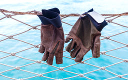 Sailing gloves hanging on the nets  of yacht  with blue ocean ba Royalty Free Stock Photos