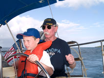 Sailing With Grandpa. Young boy steering a sailboat with grandpa watching closely Royalty Free Stock Images