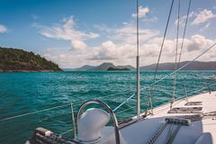 Sailing the Great Barrier Reef. Sailboat sailing on a warm beautiful day in the Whitsunday Islands on the Great Barrier Reef in Australia royalty free stock images