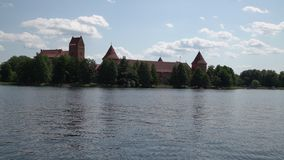Sailing through historic Trakai castle in Lithuania with a yacht on a warm summer day. Summer time activity in Galves lake with. Friends, tourist attraction stock video footage